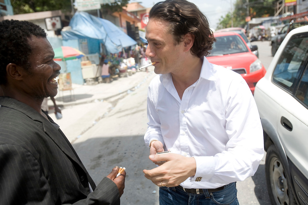 David Koubbi shares a ciggarrette with a man on the street. Koubbi, a French lawyer, is visiting Haiti to advocate to the Haitian government for passports for 56 children. The children were in the adoption process before the earthquake and though the adoptions have all been finalized, the children need passports before they can join their adopted families in France.