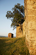 Abandoned church outside small village in Italy at sunset with red building