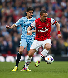 Arsenal Forward Lukas Podolski (GER) is challenged by Man City Midfielder Jesus Navas (ESP) - Photo mandatory by-line: Rogan Thomson/JMP - 07966 386802 - 29/03/14 - SPORT - FOOTBALL - Emirates Stadium, London - Arsenal v Manchester City - Barclays Premier League.