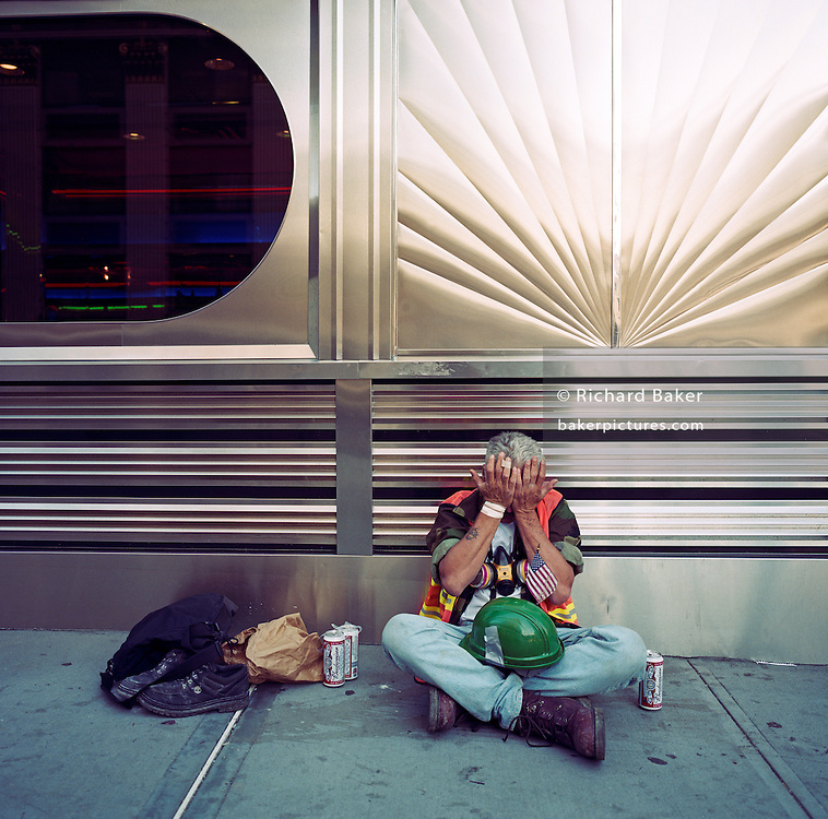Sitting drunk on a mid-town sidewalk (pavement), a construction worker wipes tears from his eyes. The man has driven from his mid-west home to offer help at the hazardous Ground Zero where for the past 4 days and nights he has been uncovering debris and human remains after the terrorist attacks on the World Trade Center. Exhausted and emotional, he was sent away for his own and the safety of others and alcohol was his first purchase. New Yorkers praised their heroes for assisting their city (and America) in their hour of need but here, passers-by stepped over him complaining of his drunken state. The now lonely man is distressed, tormented and psychologically fragile but gets no help. With his few possessions, his hard hat and flag, mask and cans of Budweiser we see a man at his lowest ebb.