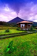 The Very Active Arenal Volcano Rises Behind A Cabin At The Lomas de Volcano Eco Lodge In La Fortuna, Costa Rica.