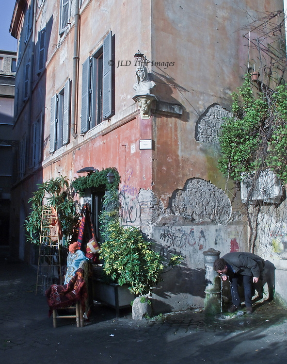 Trastevere street scene: sculpture on corner of a house, man drinking from a fountain; sculpture stuck on the wall above.