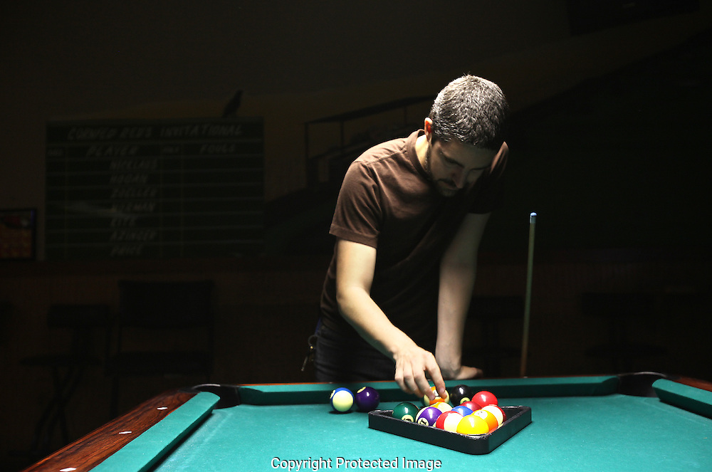 A sleepy Chris DeVille racks pool balls for a game at Cornfed Red's at 4:15 a.m.(Jodi Miller/Alive)