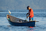 A fisherman prepares to cast a net into Lake Catemaco as a heron bird rests on the bow of his boat in Catemaco, Veracruz, Mexico. The tropical freshwater lake at the center of the Sierra de Los Tuxtlas, is a popular tourist destination and known for free ranging monkeys, the rainforest backdrop and Mexican witches known as Brujos.