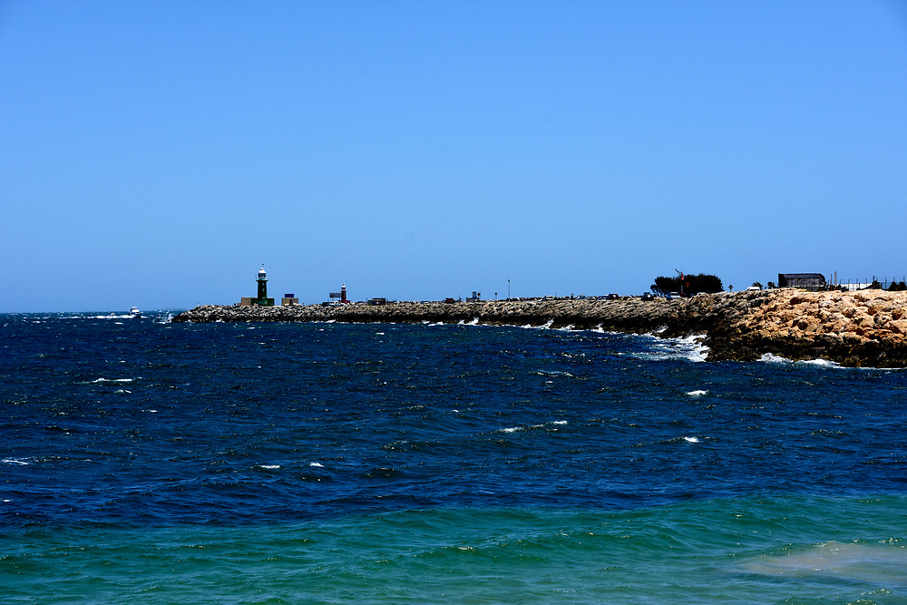 Starboard green lighthouse on a breakwater at the entrance to Freemantle harbour