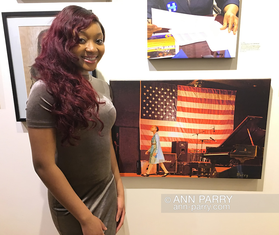 """Huntington, New York, USA. March 5, 2017. Sheimyrah Mighty, 18, next to 2008 photo of herself, at Opening Reception for """"Her Story Through Art"""" Invitational Art Show, celebrating Women's History Month, at Huntington Arts Council, Main Street Gallery. Artists Tara Leale Porter, Irene Vitale, Anahi DeCanio, Ann Parry, Show March 2 - 25, 2017."""