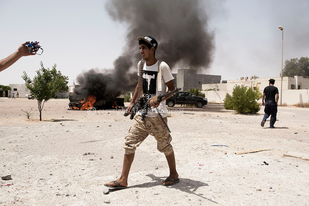 Libya: a fighters affiliated with Libya's Government of National Accord's (GNA) passes nearby a destroyed ISIS car. Alessio Romenzi