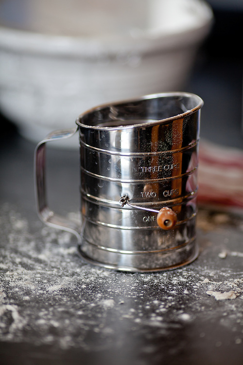 A metal flour sifter on a countertop dusted with flour.