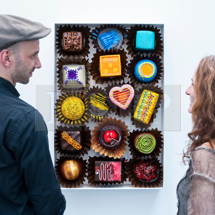"""© Licensed to London News Pictures. 19/05/2016. London, UK. Visitors view Peter Anton's """"Lustful Selection"""", a mixed media work that looks like a box of delicious chocolates.  Art16 opens at Olympia, in west London.  Now in its fourth edition, the fair brings together over 100 galleries from more than 30 countries showcasing a diverse cross-section of work by contemporary artists from around the world for buyers and art enthusiasts to visit. Photo credit : Stephen Chung/LNP"""