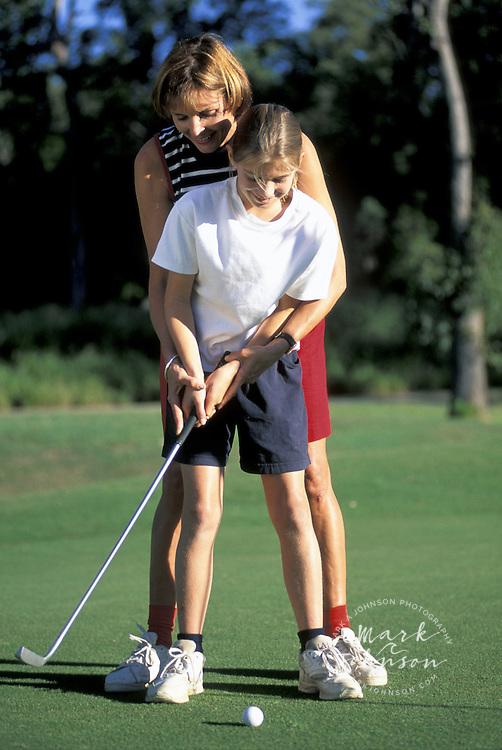 Mother teaching daughter golf, Brisbane, Queensland, Australia