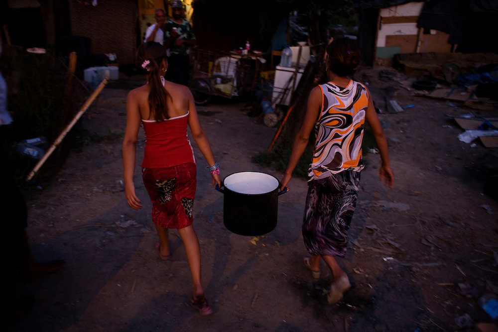 A teenage girl and her mother return home with a large stock pot filled with water. In the Stara Gazela settlement the only water source is a single tap in an apartment complex across a four lane motorway.