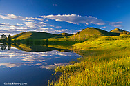 Pond reflects at days end in the Bears Paw Mountains near Havre, Montana, USA