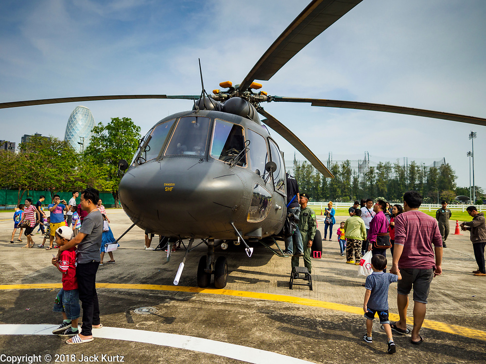 "13 JANUARY 2018 - BANGKOK, THAILAND: Thai children and their parents around a Thai Army Mi-17 ""Hip"" (NATO designation) helicopter during Children's Day activities at the Royal Thai Army's King's Guard 2nd Cavalry Camp in central Bangkok. Children's Day is called ""Wan Dek"" in Thai. Many government offices and military bases hold special activities for children as do shopping malls.       PHOTO BY JACK KURTZ"