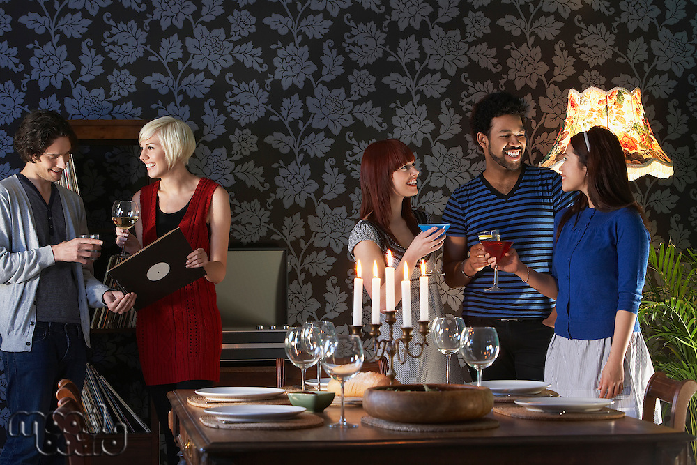 Group of people smiling standing by dining table