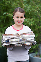 Girl (10-12) holding bundle of waste paper smiling