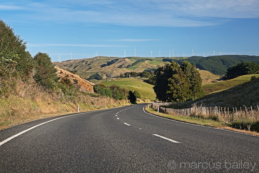 looking down the road towards the te uku windfarm on the hills of the waikato from SH23 - hamilton to raglan, waikato, new zealand