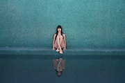 sensual woman sitting at the pool leaning next to blue tile wall