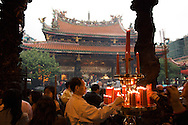 Praying at Lungshan Temple in Taipei, Taiwan is considered to be very lucky on the first day of Chinese Lunar New Year.  Many people burn incense or light candles as they pray to the various dieties of the temple.
