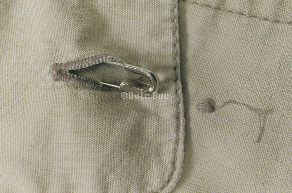 button with safety pin half through