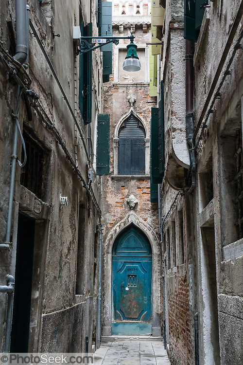 Blue door in alley dead end. Venice (Venezia), founded in the 400s AD, is capital of Italy's Veneto region, named for the ancient Veneti people from the 900s BC. The romantic City of Canals stretches across 100+ small islands in the marshy Venetian Lagoon along the Adriatic Sea, between the mouths of the Po and Piave Rivers. The Republic of Venice was a major maritime power during the Middle Ages and Renaissance, a staging area for the Crusades, and a major center of art and commerce (silk, grain and spice trade) from the 1200s to 1600s. The wealthy legacy of Venice stands today in a rich architecture combining Gothic, Byzantine, and Arab styles. Venice and the Venetian Lagoon are honored on UNESCO's World Heritage List.