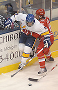 OSU's Mathieu Picard (right) holds LSSU's Brad Cooper against the boards during first period action of the Buckeyes Friday night game against the LSSU Lakers at Taffy Abel Arena in Sault Ste. Marie.