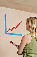 Woman holding paintibrush facing wall with painted diagram