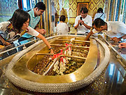 "12 JULY 2014 - PHRA PHUTTHABAT, SARABURI, THAILAND: People pray and make merit in the chapel housing a footprint of the Buddha before the Tak Bat Dok Mai at Wat Phra Phutthabat in Saraburi province of Thailand. Wat Phra Phutthabat is famous for the way it marks the beginning of Vassa, the three-month annual retreat observed by Theravada monks and nuns. The temple is highly revered in Thailand because it houses a footstep of the Buddha. On the first day of Vassa (or Buddhist Lent) people come to the temple to ""make merit"" and present the monks there with dancing lady ginger flowers, which only bloom in the weeks leading up Vassa. They also present monks with candles and wash their feet. During Vassa, monks and nuns remain inside monasteries and temple grounds, devoting their time to intensive meditation and study. Laypeople support the monks by bringing food, candles and other offerings to temples. Laypeople also often observe Vassa by giving up something, such as smoking or eating meat. For this reason, westerners sometimes call Vassa ""Buddhist Lent.""     PHOTO BY JACK KURTZ"