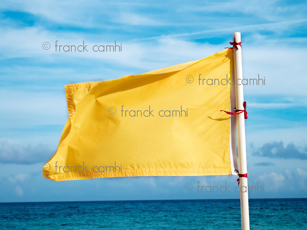 yellow flag on the sea meaning that swimming is dangerous