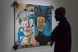 "© Licensed to London News Pictures. 20/09/2017. London, UK. A man views ""Dos Cabezas"", 1982, by Jean-Michel Basquiat. Preview of ""Basquiat: Boom for Real"", the first large-scale exhibition in the UK of the work of American artist Jean-Michel Basquiat (1960-1988) taking place at the Barbican Art Gallery, 21 September-28 January 2018. Photo credit : Stephen Chung/LNP"