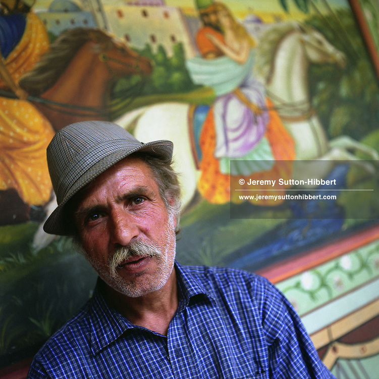A Roma elder sits in front of a scene from a Persian story painted on the wall of his home, in the old part of the Sintesti Roma camp.  These Arabian scenes are very popular as wall decoration, but no-one within the camp knows the reason why they were first painted...