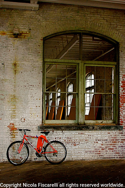 A parked new bike in front of an old Roebling  manufucturing company in Trenton Nj.