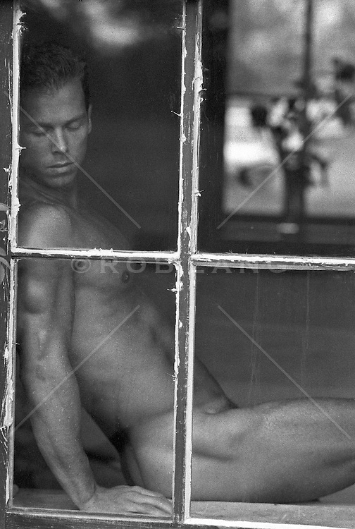 naked man resting by a window