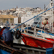 Harbour, Tangier, Morocco, pictured on December 27, 2009. A fisherman works on his boat. Beyond the harbour the city rises in its jumble of new and old buildings.  Tangier, the 'White City', gateway to North Africa, a port on the Straits of Gibraltar where the Meditaerranean meets the Atlantic is an ancient city where many cultures, Phoenicians, Berbers, Portuguese and Spaniards have all left their mark. With its medina, palace and position overlooking two seas the city is now being developed as a tourist attraction and modern port. Picture by Manuel Cohen