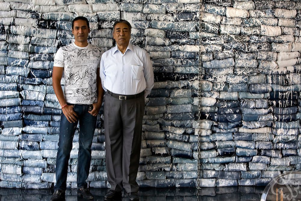 Air Marshal Man Mohan Sinha, chairman of Velocity Apparelz CO (r) poses for a photograph with his son, and CEO of parent company Vogue International Agencies FZE, Siddharth Sinha in front of a creative wall of painted jeans that Siddharth designed at the Velocity factory in Ismailia (130 kilometers north of Cairo, Egypt) October 27, 2008.  The Sinhas are Indian businessmen who have been operating their jeans company in Egypt since 2001, employing 2700 Egyptian workers while supplying jeans to major companies that include Levis, Target, and Zara.