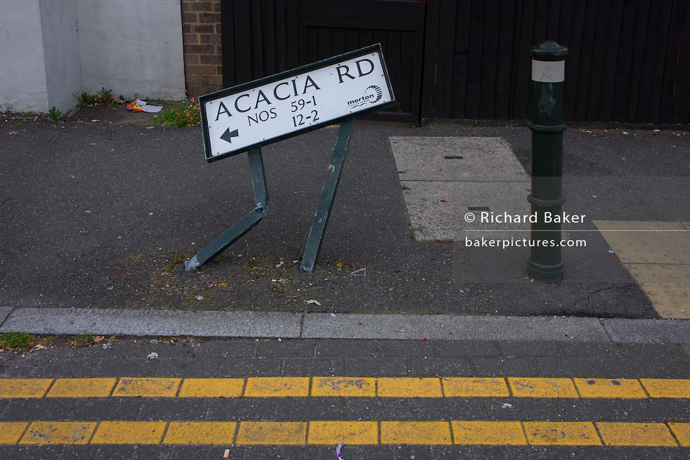 A bent street sign for Acacia Road in Mitcham, London borough of Merton.