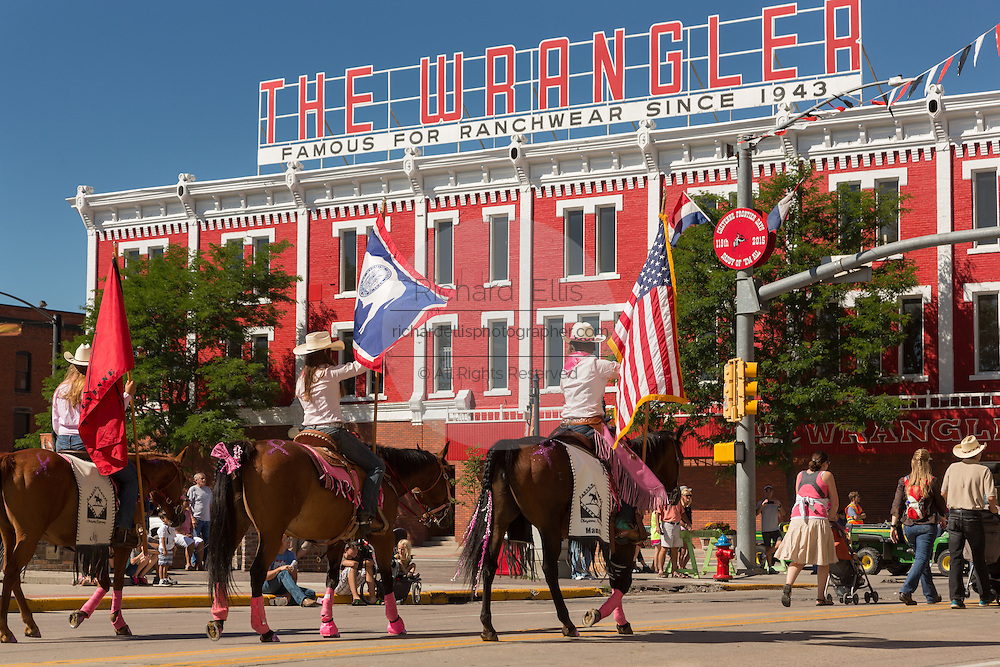 Cowboys on horseback ride past the Wrangler western wear store during the Cheyenne Frontier Days parade through the state capital July 23, 2015 in Cheyenne, Wyoming. Frontier Days celebrates the cowboy traditions of the west with a rodeo, parade and fair.