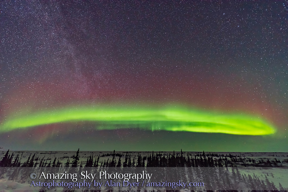 A visually dim auroral arc across the northern sky, with the Milky Way at left in the northwestern sky, from Churchill, Manitoba, on February 14, 2018. Polaris is at top, left of centre. This illustrates the classic auroral oval across the north, centred due north at this longitude, below Polaris. <br /> <br /> This is a single exposure with the Sigma 14mm lens at f/1.8.