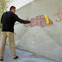 Toluca, Méx.- Con resignación este jóven trata de limpiar los grafittis que fueron pintados en la pared de su casa de la colonia Altamirano. Agencia MVT / Mario Vázquez de la Torre.