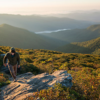 Sunrise at the top of Craggy Pinnacle Trail along the Blue Ridge Parkway northeast of Asheville, North Carolina. A local transplant (model released) walking during the first sunrise he has watched since moving to Asheville four years ago.