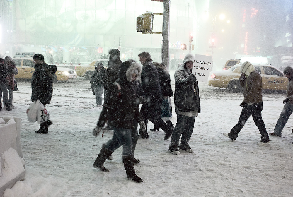 Man holding sign advertising stand-up comedy during heavy winter storm on December 19, 2009, Times Square, NY