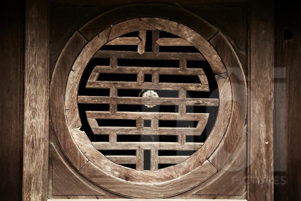 Wooden carved window in tomb complex. Vietnam, Asia