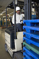 Man driving fork lift truck in newspaper factory