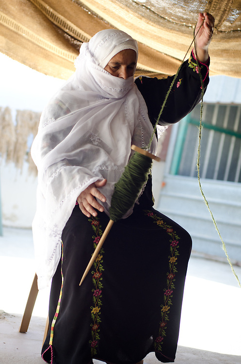 A Bedouin woman using traditonal wool spinning techniques works at the Sidreh weaving co-operative in Lakiya, Israel. The co-op provides jobs to local women, and uses its profits to support women's literacy and health projects in Bedouin villages in the Negev desert.