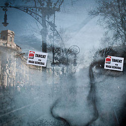 "Two stickers are pasted over the eyes of a advertisement in Barcelona that read, ""Closed for General Strike""."