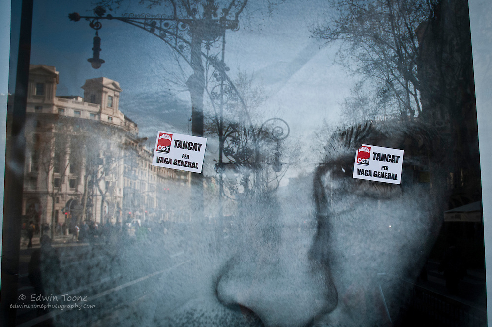 """Two stickers are pasted over the eyes of a advertisement in Barcelona that read, """"Closed for General Strike""""."""
