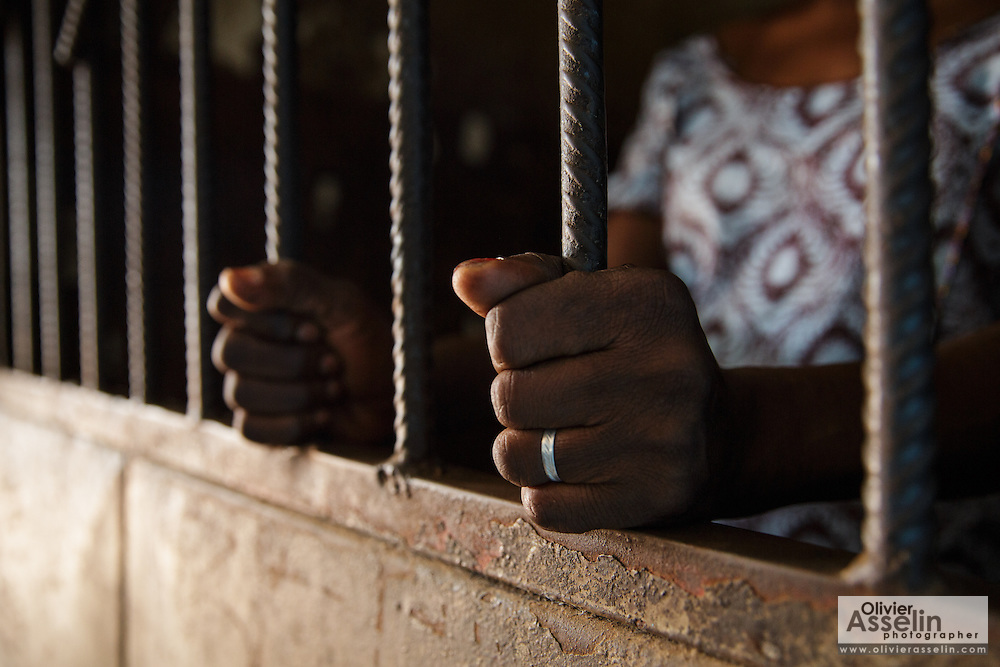Photo illustration showing a woman holding the bars of a prison cell at the police station in Katiola, Cote d'Ivoire on Saturday July 13, 2013. In July 2012,  for the first time ever in the country, nine women were arrested and jailed for performing genital mutilation on girls.