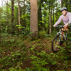 A woman rides her mountain bike at Moose Brook State Park in Gorham, new Hampshire.