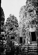 Khmer nun sitting beneath the Towers of Bayon.  ..There are 37 standing towers, most but not all with four carved faces oriented toward the cardinal points.