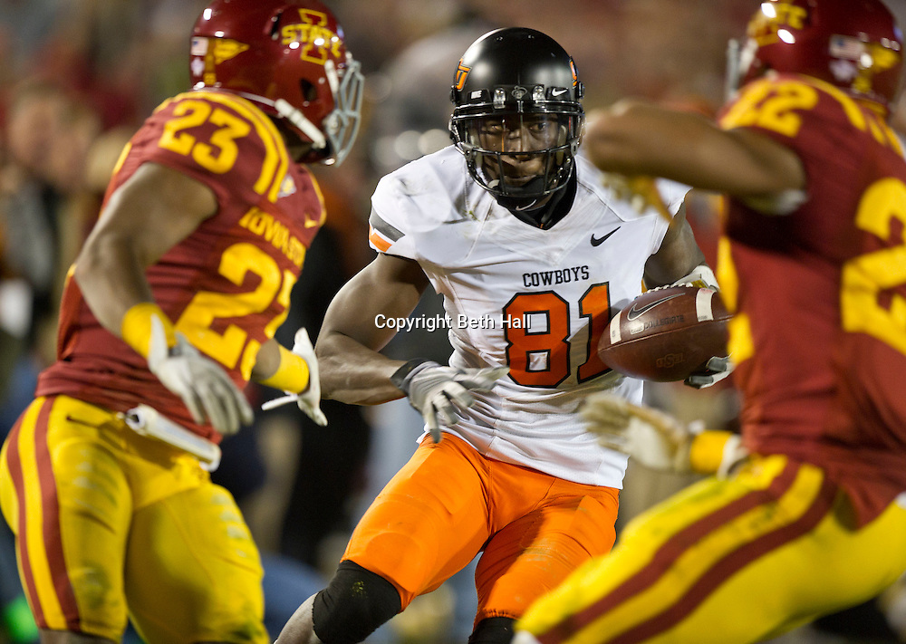Nov 18, 2011; Ames, IA, USA; Oklahoma State Cowboys wide receiver Justin Blackmon (81) carries the ball against Iowa State Cyclones  defensive backs Leonard Johnson (23) and another defender during the first half at Jack Trice Stadium. Iowa State defeated Oklahoma State 37-31. Mandatory Credit: Beth Hall-US PRESSWIRE Editorial sports photography of the Iowa State Cyclones vs. Oklahoma State Cowboys in 2011 in Aimes, Iowa.