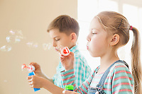 Brother and sister playing with bubble wands at home